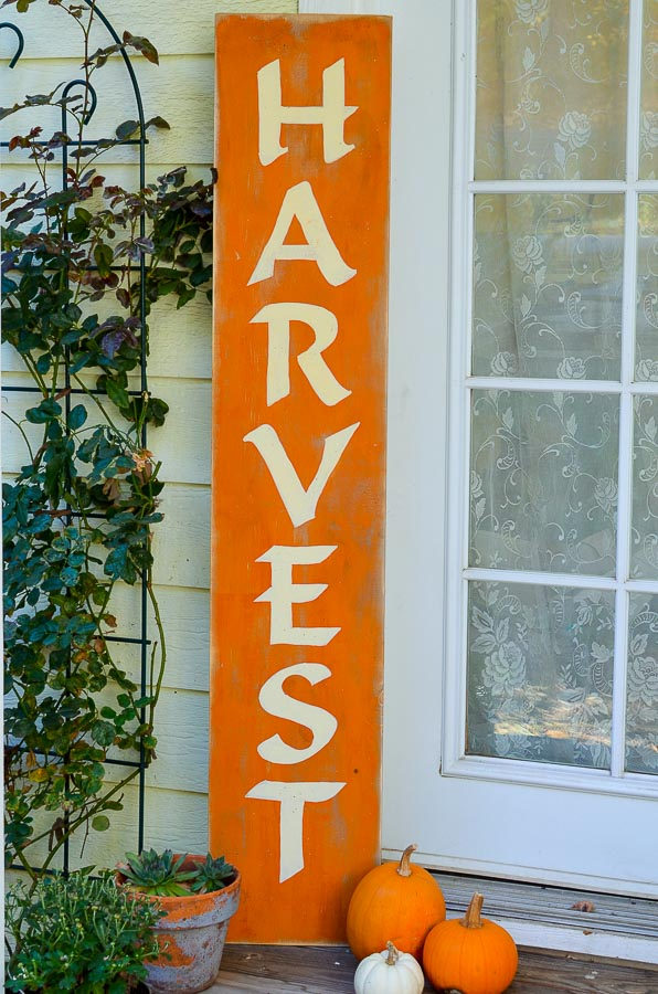 DIY harvest sign setting on the porch with pumpkins and fall plants