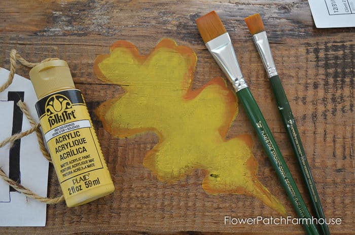 painted oak leaf with paint bottle and brushes
