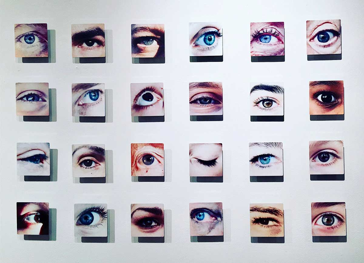 A mural of 24 different eyes cover a plain white wall.