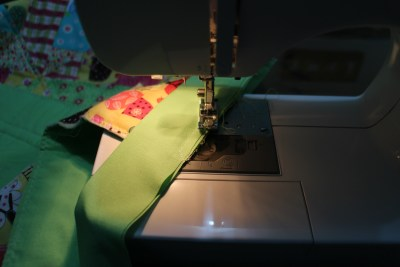 With the cut edges together sew the binding on stopping about a quarter of an inch from the corner and sew diagonally off the edge.