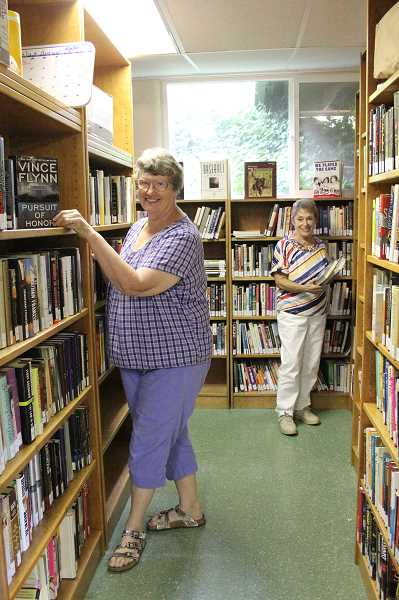 Photo Credit: LINDSAY KEEFER - Photo by Lindsay Keefer Josie Hyde (left) and Jan Metzger work on filling the shelves of the newly opened North Marion Community Library located in the basement of Aurora Presbyterian Church. The library will have its grand opening from 10 a.m. to 2 p.m. Saturday.