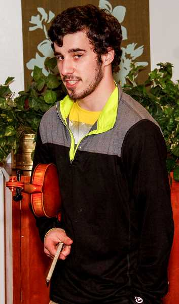 Pacific University junior Tyler Goldman learned of the Forest Grove United Church of Christ's homeless shelter through his Civic Engagement course. Goldman decided to put his violin skills to good use by playing for the folks at the shelter. 'I just want to give back to the community,' he said.