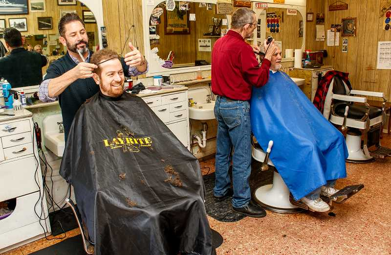 HILLSBORO TRIBUNE PHOTOS: TRAVIS LOOSE - Barber Joe Celaya (standing left) cuts Conner Heltons hair while shop owner Bruce Reedy (standing right) works on Richard Gaumone Saturday, March 26.  Every barbershop in town has its unique clientele, Celaya said. We get the rest.