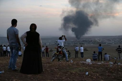 Smoke rises in the Syrian town of Kobani as Turkish Kurds watch near the Mursitpinar border crossing on the Turkish-Syrian border in the southeastern town of Suruc