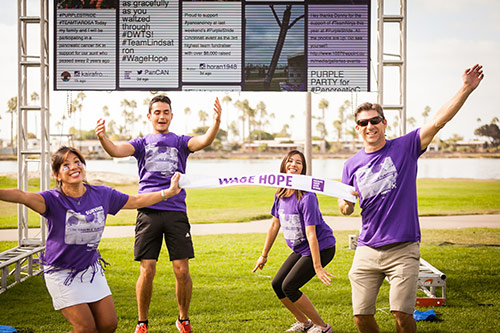 Anggie jumping for joy with her family at PurpleStride San Diego.