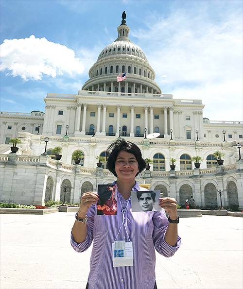 Pancreatic cancer advocate smiles in front of the U.S. Capitol building holding up photos of her loved ones