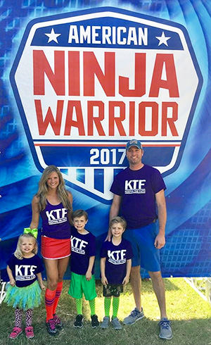 Brandi Monteverde with her three young children and husband on the set of American Ninja Warrior wearing family team shirts