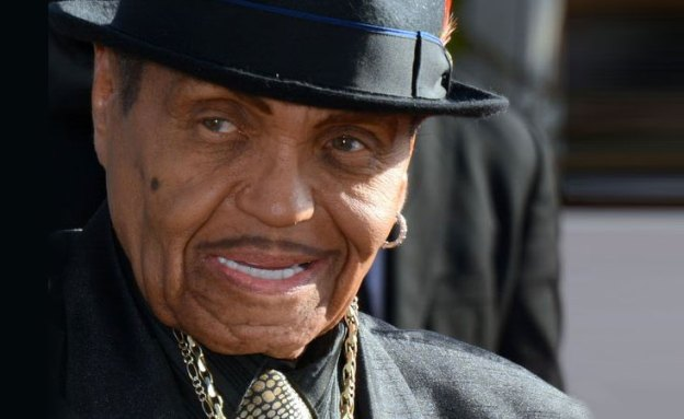 Joe Jackson smiling toward the left at a camera