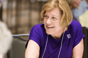 PanCAN's Chief Science Officer Lynn Matrisian, PhD, speaks with attendees at an event table.