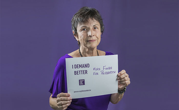 Survivor holds a sign saying she supports more pancreatic cancer research funding.