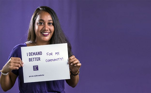 Volunteer holds a sign saying why she Demands Better for pancreatic cancer patients