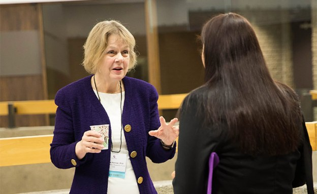 Barbara Kenner, PhD, speaks with a conference attendee about pancreatic cancer research