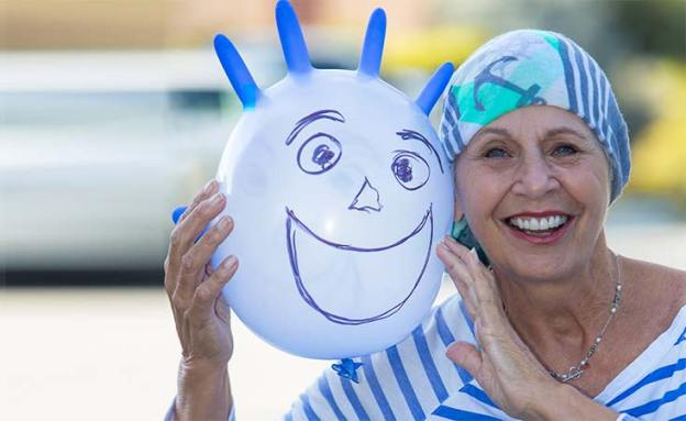 "Pancreatic cancer survivor poses with ""chemo buddy,"" an inflated latex glove with a happy face"