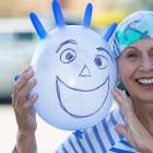 """Pancreatic cancer survivor poses with """"chemo buddy,"""" an inflated latex glove with a happy face"""