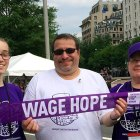"Pancreatic cancer survivor holds ""Wage Hope"" banner with his wife and daughter at PurpleStride"