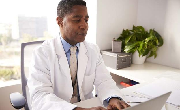 African-American male doctor assesses a patient's risk for developing pancreatic cancer