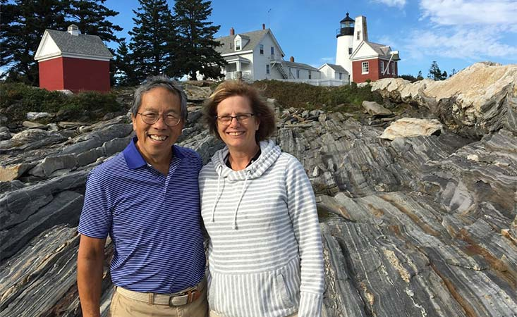 Pancreatic cancer caregiver and her husband in front of a lighthouse in Maine during vacation