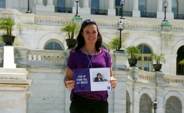 Advocacy Day volunteer at U.S. Capitol with photo of parents who died from pancreatic cancer