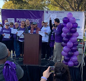 Doug Kelley on stage being honored as a PurpleStride Grand Club Member