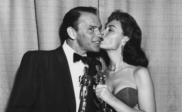 Black and white photo of Donna Reed and Frank Sinatra with their Oscars