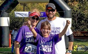 Young Caucasian mom, dad and daughter at outdoor fundraising event