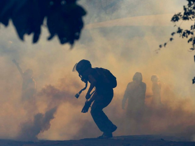 """An anti-government protester runs amidst tear gas launched by the police during a protest in Caracas March 12, 2014. Supporters and foes of Venezuelan President Nicolas Maduro took to the streets of Caracas again on Wednesday a month after similar rival rallies brought the first bloodshed in a wave of unrest round the OPEC member nation. Red-clad sympathizers of Maduro's socialist government held a """"march for peace"""" while opponents wearing white gathered to denounce alleged brutality by security forces during Venezuela's worst political troubles for a decade. REUTERS/Tomas Bravo (VENEZUELA - Tags: POLITICS CIVIL UNREST TPX IMAGES OF THE DAY)"""
