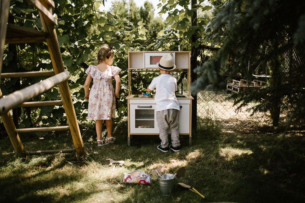 Dzieci bawią się kuchenką w ogrodzie na urodzinach w stylu boho