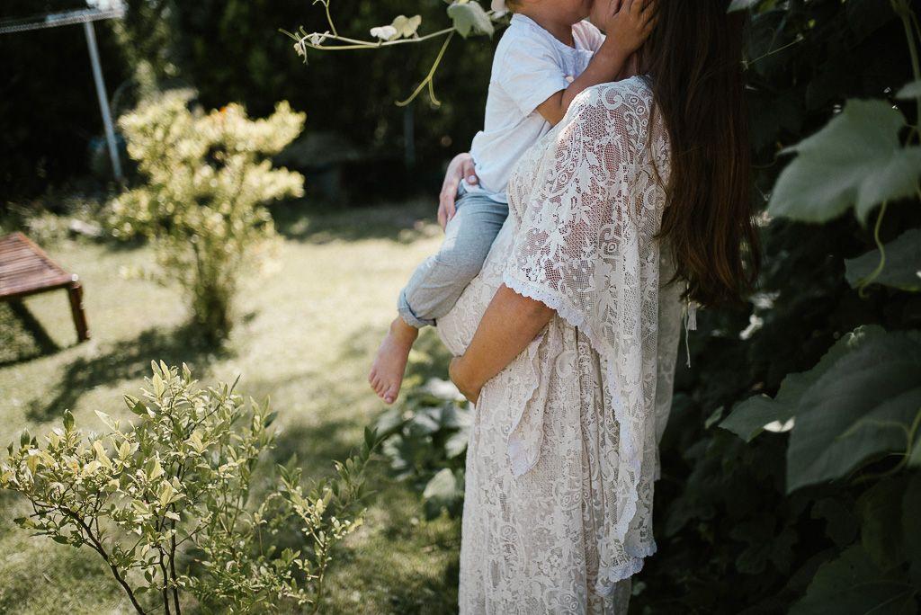 Kobieta w ciąży w sukni w stylu boho trzyma syna na rękach