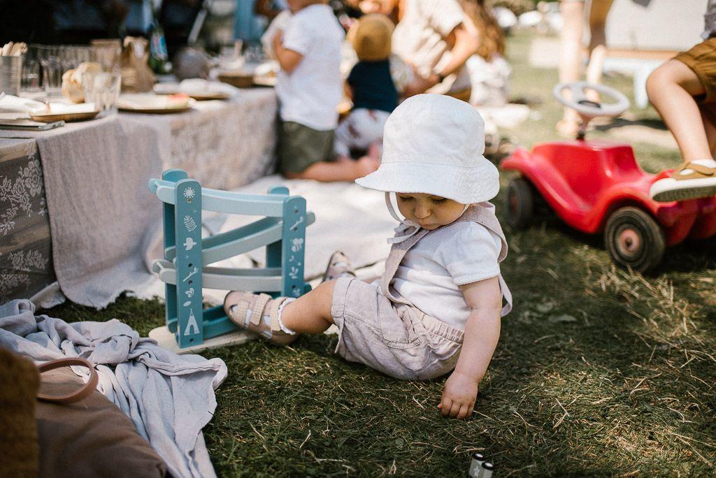 Dziewczynka siedzi na trawie na imprezie urodzinowej w ogrodzie