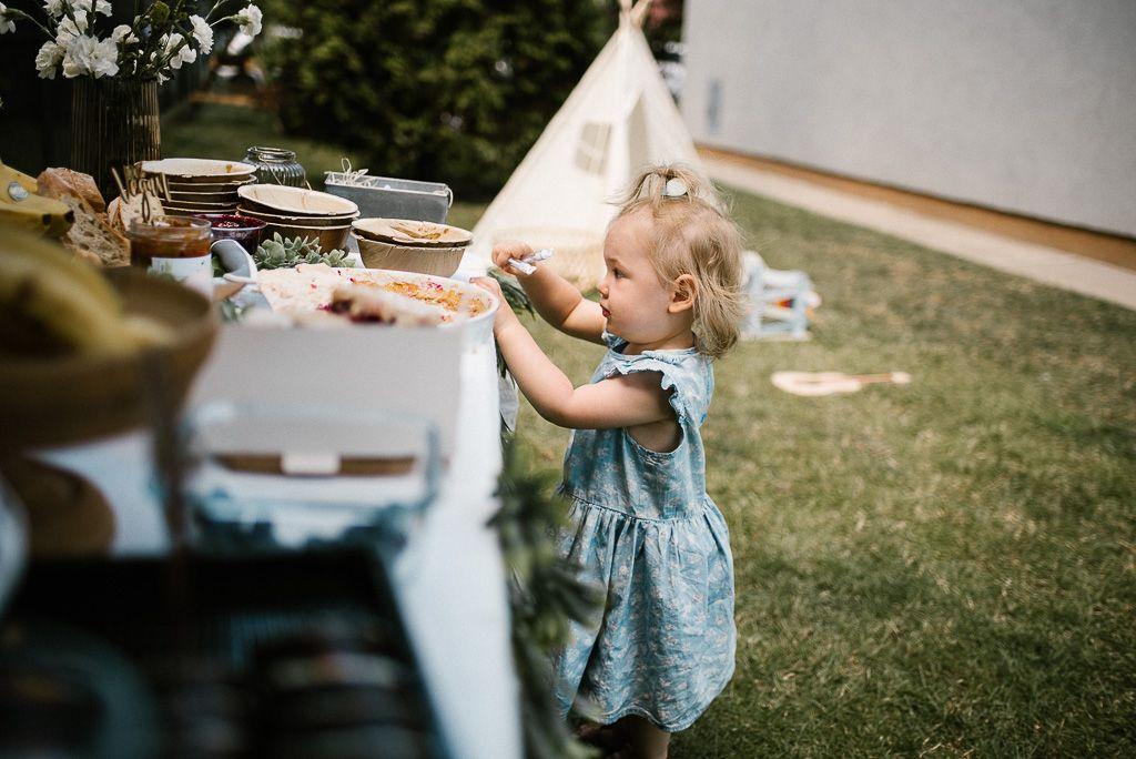 Dziewczynka przy stole szwedzkim na pikniku boho