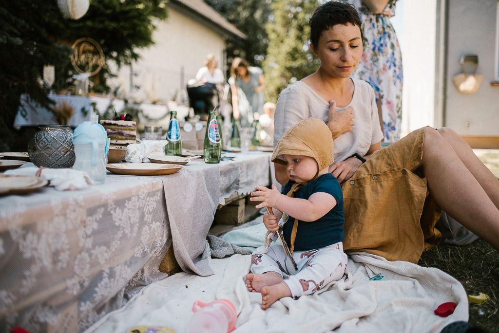 Mama z chłopcem siedzą przy stole na podłodze na pikniku boho