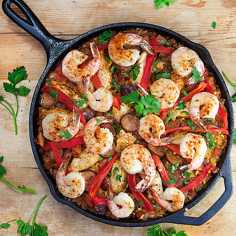 Spanish Paella in a cast iron skillet, showing 14 shrimp on top decorated with strips of sliced red bell pepper and parsley sprigs