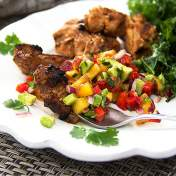 Mexican spiced grilled chicken and tropical salsa on a white plate