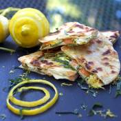 smoked salmon quesadillas on a slate board with a lemon and a swirl of lemon zest