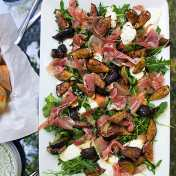 big rectangular platter of grilled figs, prosciutto and burrata on a bed of arugula