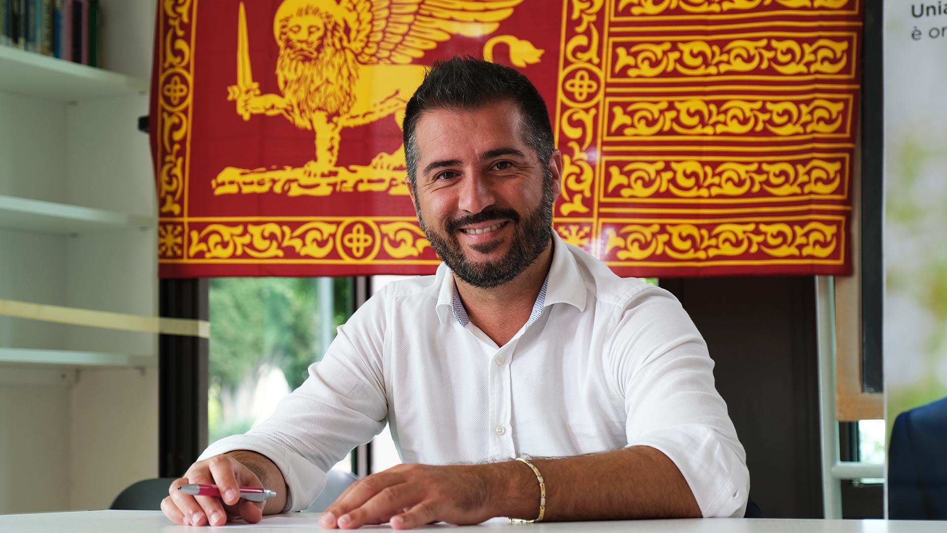 Paolo Borchia con sullo sfondo la baniera di San Marco