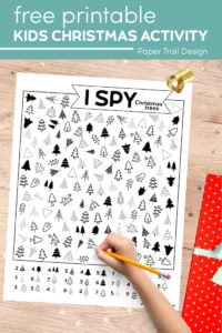 I spy Christmas tree themed activity and kid's hand holding pencil with text overlay- free printable kids Christmas activity