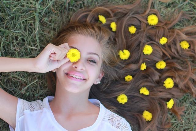 Mädchen liegend auf der Wiese mit gelben Blumen im Haar, lachend