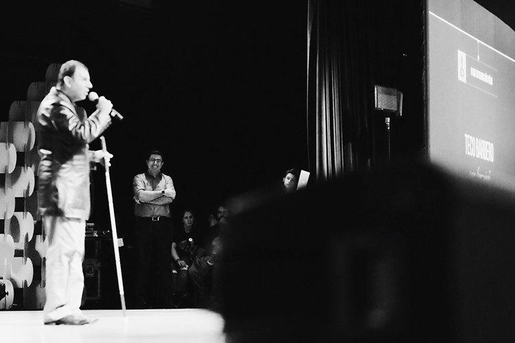 Teco Barbero sendo assistido de camarote pelo fotógrafo André Mansano. Descrição da Imagem: Teco Barbero está no grande palco do Centro de Convenções Anhembi, e ao fundo o fotógrafo André Mansano sorri ao ouvir a história contada por ele.