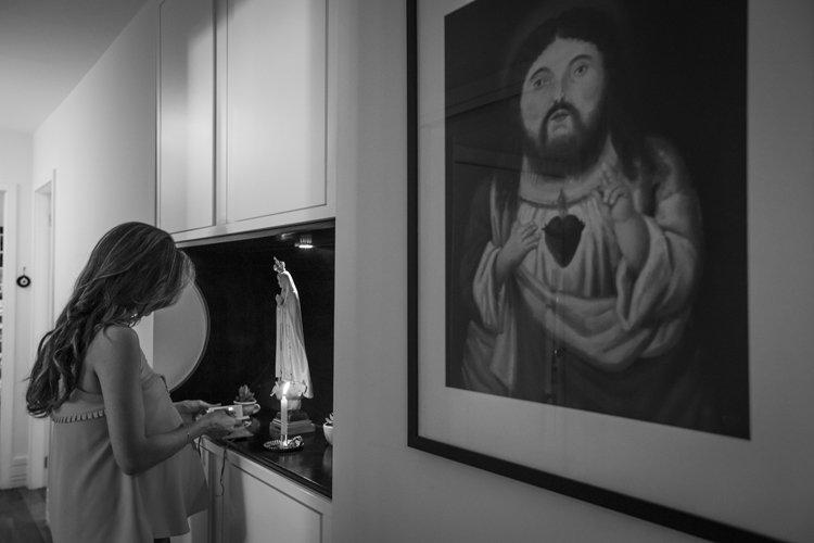 Fotografia: Grazi Ventura. Descrição da Imagem: Uma mulher grávida, acendendo uma vela para sua oração e ao seu lado um quadro com a imagem de Jesus Cristo.