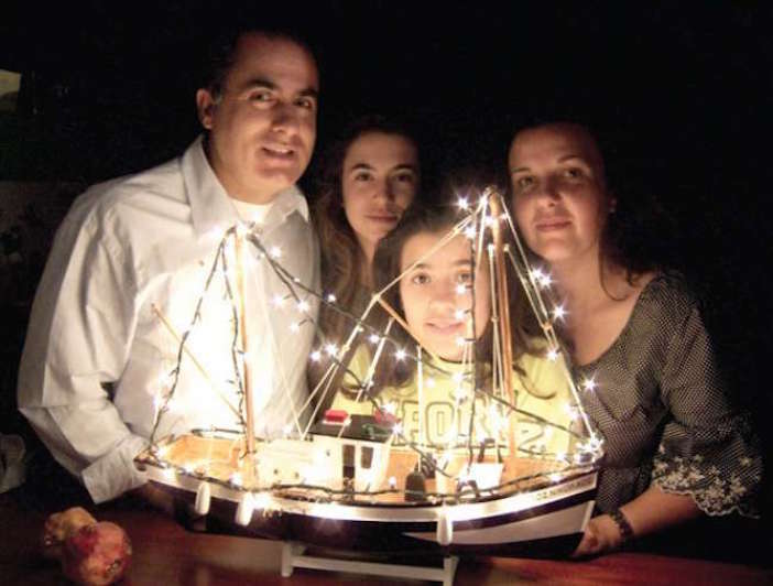 Sotiris, his wife Anna and their two daughters Eleanor and Joanne with the traditional Greek Christmas boat which will carry their hopes and dreams.Photo Mike Sweet
