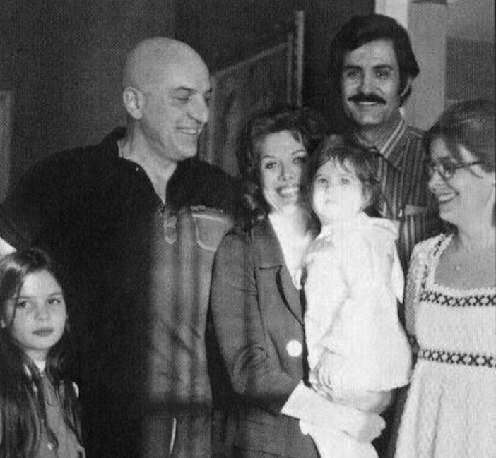 Baby Jennifer Aniston in her mom's arms, with dad John in the background and a smiling godfather, Telly Savalas