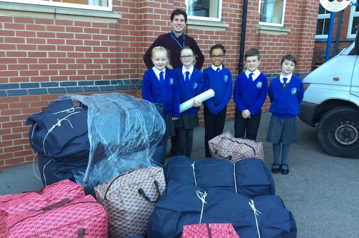 Shepshed, England elementary school students with some of the clothing they collected for refugee camps in northern Greece.