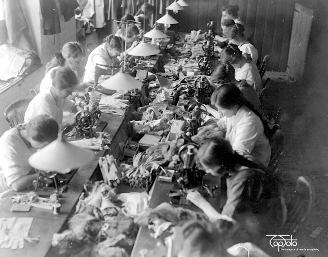 Glove Making At Witney. Machine Department - sewing, buttoning and button holing the gloves. Much work is done in the factory and in outlying villages by old employees who wish to continue after marriage.