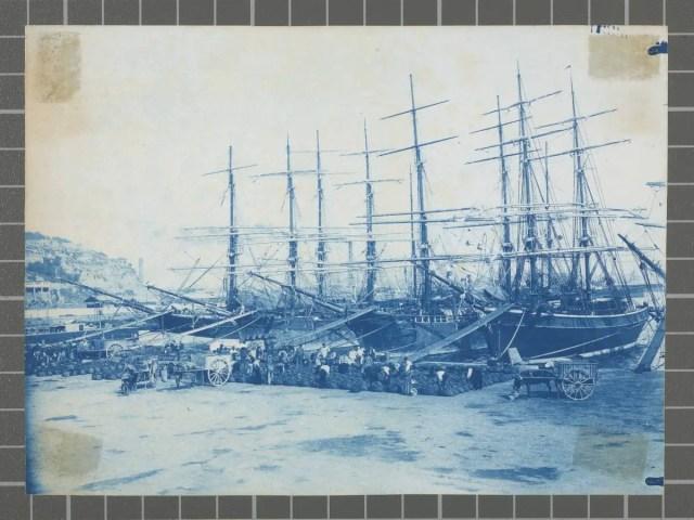 Vista del port de Barcelona. S'observen vaixells de vela i estibadors treballant al port.