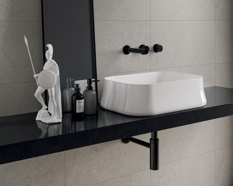 Długi blat łazienkowy zumywalką nablatową pięknie prezentują się natle płytek ceramicznych zefektem terrazzo.