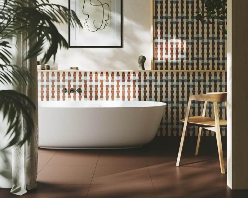 Mozaika wkształcie gorsecików, opięknym kolorze beżu iochry wprowadza downętrz wstylu modernistycznym element dynamiki iruchu.