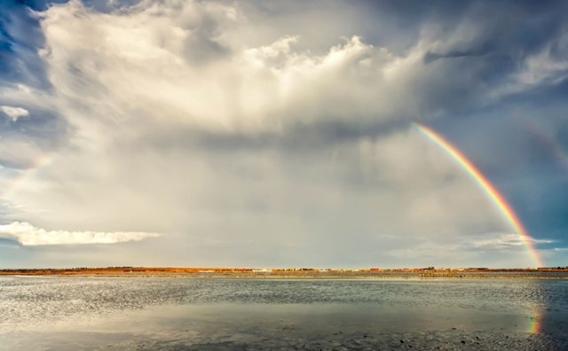 Landscape with a double rainbow from a lake