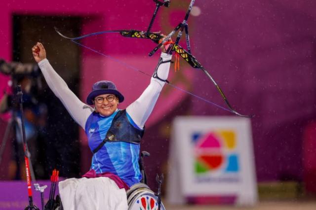Female archer raises arms in triumph