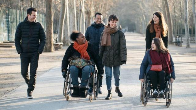 Group of people including two women in a wheelchair walking and smiling in a park
